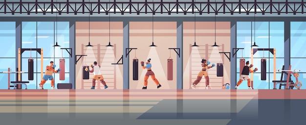 Mix race boksers doen oefeningen met bokszak training gezonde levensstijl boksen concept moderne strijd club interieur