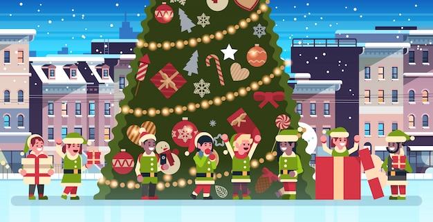 Mix race elfen groep in de buurt van versierde fir tree city gebouw huizen