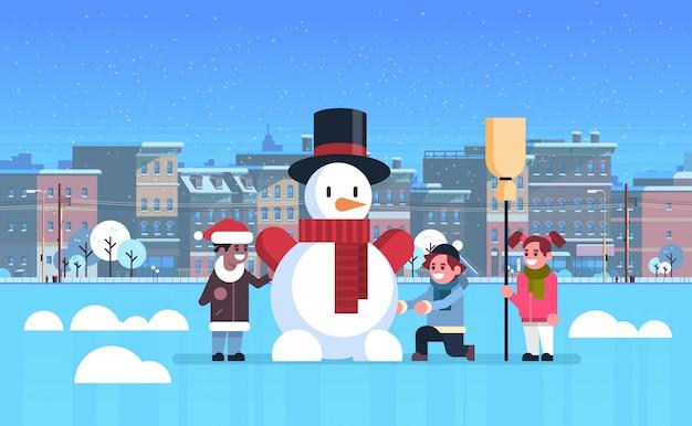 Mix race kinderen maken sneeuwpop voor kerstmis gelukkig nieuwjaar