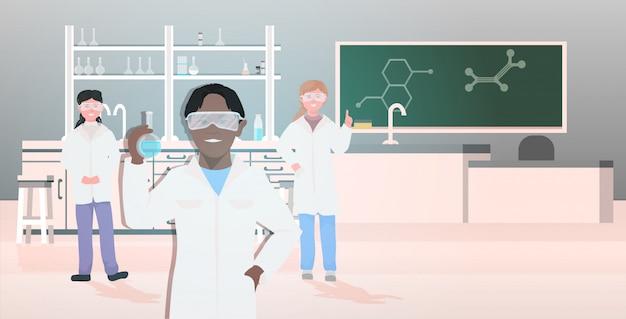 Mix race leerlingen in uniform houden reageerbuizen werken in chemisch laboratorium moderne wetenschap klas interieur horizontaal