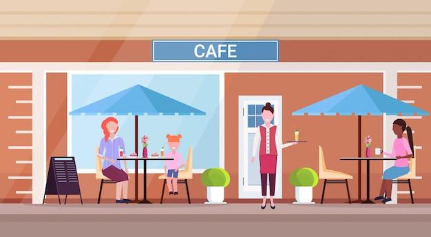 Mix race mensen bezoekers zitten modern zomer cafe winkel serveerster bedienen gasten straat restaurant terras buiten cafetaria buitenkant vlak horizontaal volledige lengte