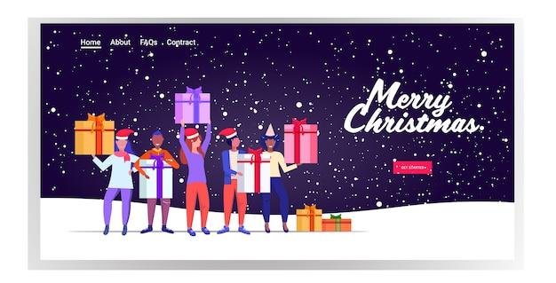 Mix race mensen in kerstman hoeden houden geschenk huidige dozen vrolijk kerstfeest gelukkig nieuwjaar wintervakantie viering