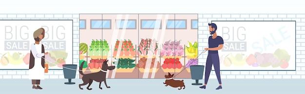 Mix race mensen lopen met honden plezier voor supermarkt winkelcentrum kruidenier buitenkant volledige lengte horizontale banner