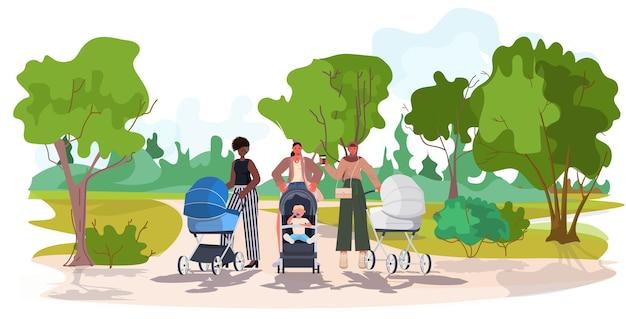 Mix race moeders lopen met pasgeboren baby's in kinderwagens moederschap concept stadspark landschap-achtergrond