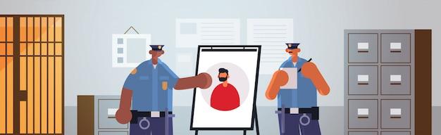 Mix race politieagenten officieren paar kijken naar bord met dief foto veiligheid autoriteit justitie dienst concept moderne politie afdeling interieur vlakke portret horizontaal