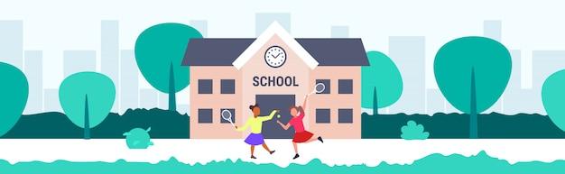 Mix race schoolmeisjes tennissen voor schoolgebouw basisschoolkinderen plezier terug naar school concept stadsgezicht achtergrond volledige lengte horizontaal