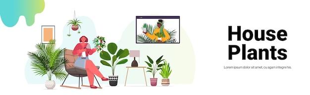 Mix race vrouwen die voor kamerplanten zorgen meisjes met virtuele bijeenkomst tijdens videogesprek woonkamer interieur horizontale kopie ruimte