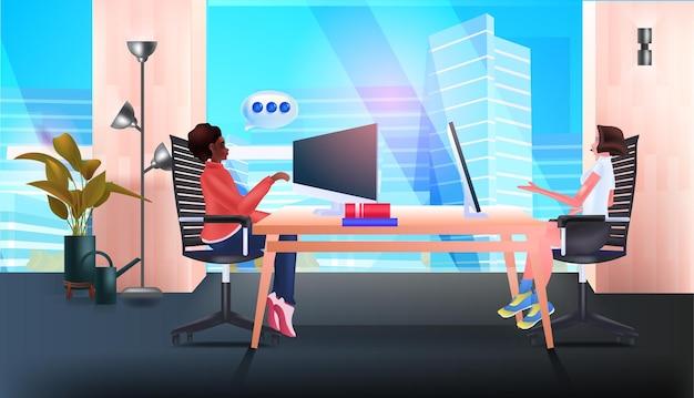 Mix race zakenvrouwen met behulp van computers op de werkplek chat bubble communicatie teamwerk sociale media netwerk concept kantoor interieur horizontale vectorillustratie