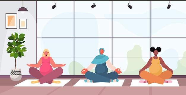 Mix race zwangere vrouwen doen yoga fitness oefeningen opleiding gezonde levensstijl concept meisjes mediteren samen moderne studio interieur