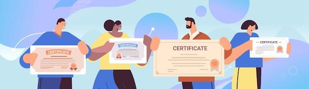 Mix ras afgestudeerde ondernemers met certificaten gelukkige afgestudeerden vieren academisch diploma graad bedrijfsonderwijs concept horizontaal portret