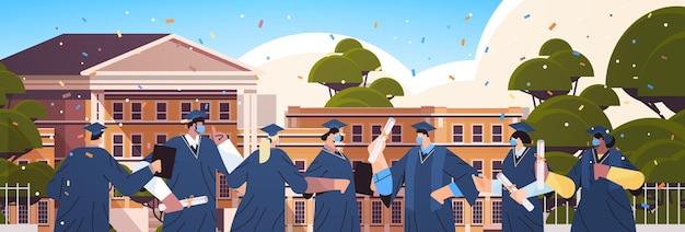 Mix ras afgestudeerde studenten in maskers die samen staan in de buurt van afgestudeerden van het universiteitsgebouw die academische diploma's onderwijs vieren