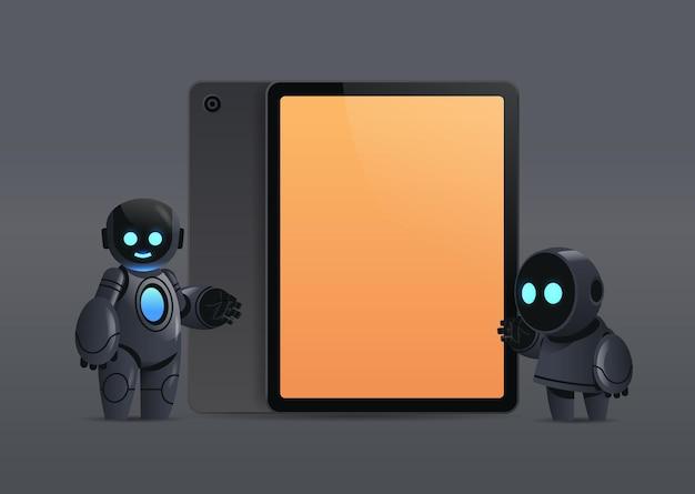 Moderne robots koppelen staande in de buurt van tablet-pc met leeg scherm robotachtig karakter kunstmatige intelligentie technologie