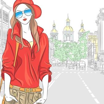 Modieus aantrekkelijk meisje in rode blouse, pet en bril in de straat in sint-petersburg