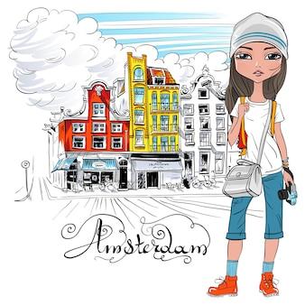 Modieuze hipster meisje toerist in een leren jas, jeans en rode laarzen lopend onderaan de straat in amsterdam met traditioneel nederlands huis, holland, nederland.