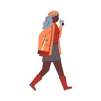 Modieuze jonge vrouw die in regenlaarzen langs de herfststraat loopt