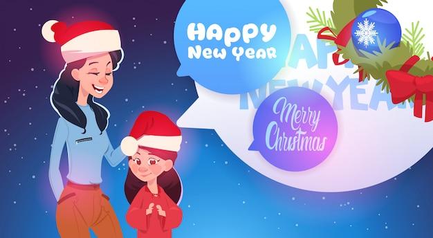 Moeder en dochter dragen santa hoeden merry christmas en gelukkig nieuwjaar wenskaart familie