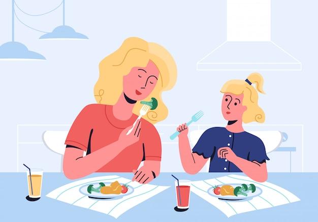 Moeder en dochter genieten van hun maaltijd, bestaande uit tomaten, bloccoli, aardappelpuree. moeder laat door eigen voorbeeld zien hoe belangrijk het is om gezond te eten. kieskeurige eter en slechte eetlustproblemen.