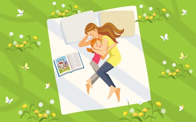 Moeder en dochter in de natuur. gelukkige familie tijd doorbrengen op het gazon lezen van boeken en ontspannen. concept moederschap opvoeding. zoete dromen.