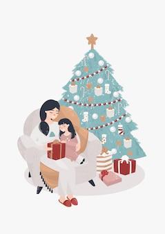 Moeder en dochter zitten in een stoel bij de kerstboom met geschenken