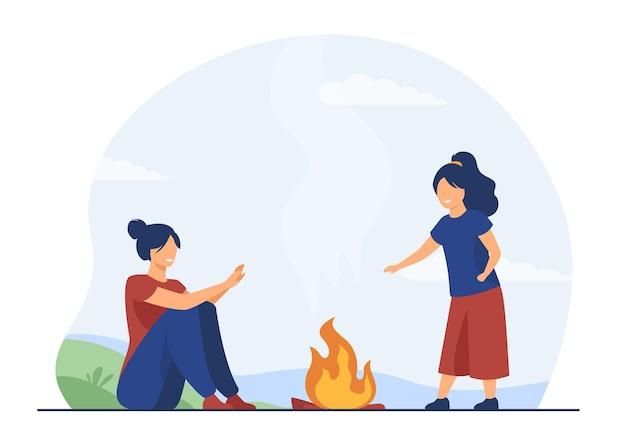 Moeder en kind genieten van kamperen buiten. gelukkige vrouw en meisje verwarmende handen bij brand. cartoon afbeelding