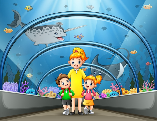 Moeder en kinderen lopen door het onderwatermuseum