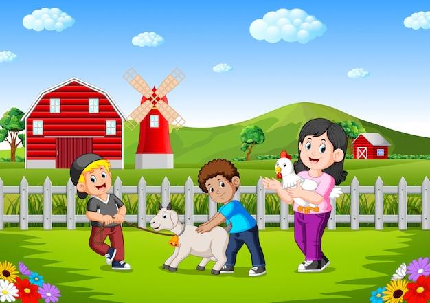 Moeder en kinderen op de boerderij met dieren