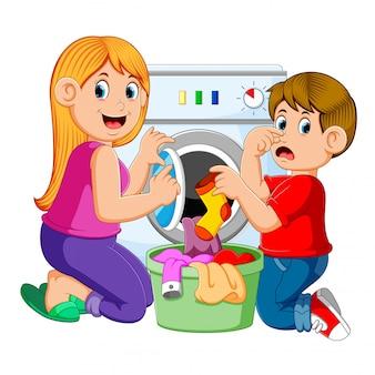 Moeder en zoon die wasserij doen