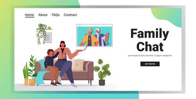 Moeder en zoon hebben virtuele ontmoeting met grootouders in webbrowservenster tijdens videogesprek familiechat communicatieconcept woonkamer interieur horizontaal