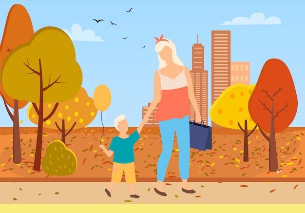 Moeder en zoon peuter lopen stadspark herfst bomen