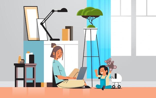 Moeder freelancer thuis werken met behulp van laptop dochtertje spelen met speelgoed coronavirus quarantaine