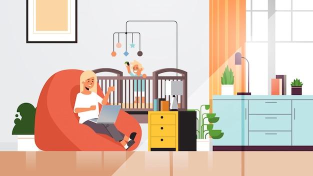 Moeder freelancer thuis werken met laptop zoontje spelen met speelgoed coronavirus quarantaine
