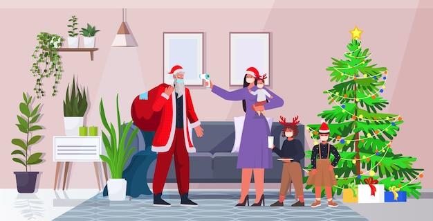Moeder met kinderen controleert lichaamstemperatuur van de kerstman coronavirus quarantaine zelfisolatie concept nieuwjaar kerst vakantie viering woonkamer interieur