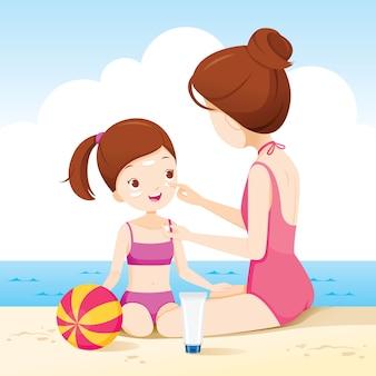 Moeder met zonnebrandcrème op dochter gezicht op het strand