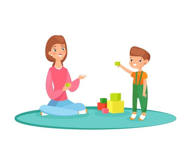 Moeder speelt blokken met haar zoon op het tapijt. thuis spelen, tijd met familie, oppas met kind.