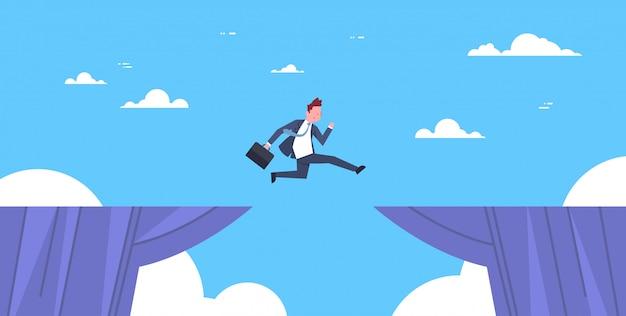 Moedige zakenman springen over cliff kloof bedrijf tot succes risico en gevaar concept
