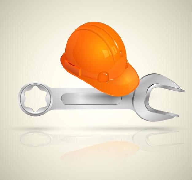 Moersleutel en helm voor fabrieksarbeider