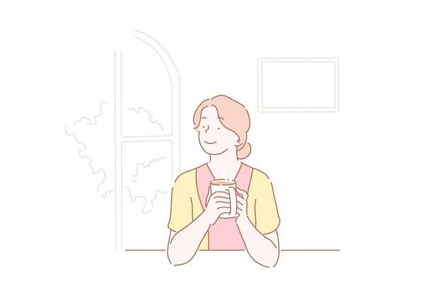 Mooi meisje dat een kop van koffie drinkt bij keuken.