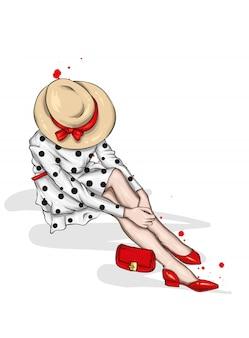 Mooi meisje in een stijlvolle jurk met een vintage hoed, handtas en schoenen.