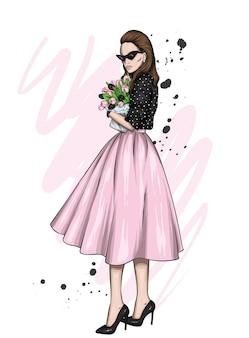 Mooi meisje in stijlvolle kleding en met bloemen