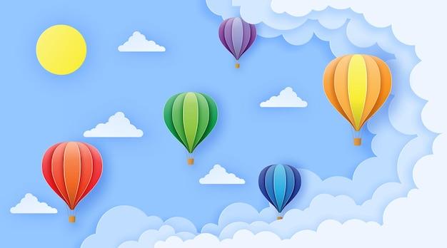 Mooie ballonnen vliegen over pluizige wolken in de blauwe lucht naar de zon