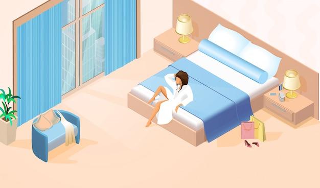 Mooie dame in witte badjas op tweepersoonsbed