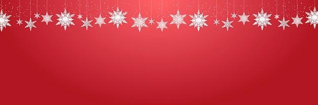 Mooie hangende sneeuwvlokken en vallende sneeuw op rood pak als achtergrond voor kerstmis, nieuwjaar en winterbanner, groetkaart