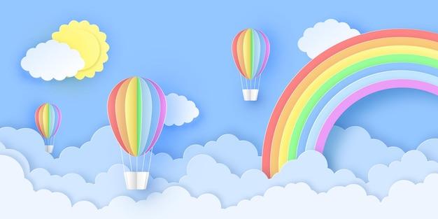 Mooie heteluchtballonnen die over pluizige wolken in de lucht vliegen met zon en regenboog