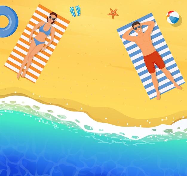 Mooie jonge vrouw en man die op het strand zonnebaden