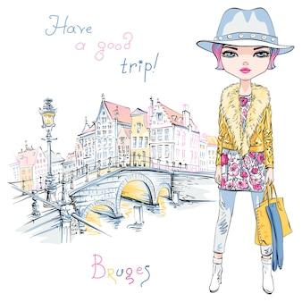 Mooie mode hipster meisje in winterkleren met tas in brugge