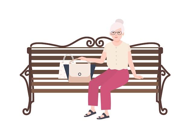 Mooie oude dame of grootmoeder zittend op straatbank