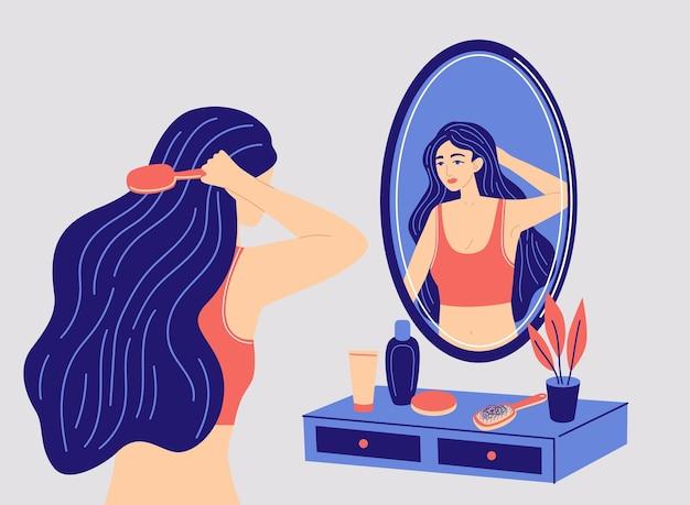 Mooie vrouw die haar lange haar kamt voor een spiegel meisje kijkt naar haar spiegelbeeld