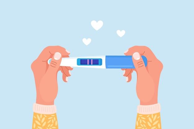 Mooie vrouwelijke hand houdt een zwangerschaps- of ovulatietest met positief resultaat als een twee lijnen. zwangere vrouw wachtende bevalling. een baby-, moederschap- en zorgconcept plannen