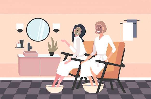 Mooie vrouwen die gezichtsmaskers en voetenbassinmeisjes in badjassen toepassen die huidverzorging spa-behandeling ontspannen