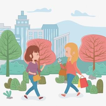 Mooie vrouwen die in het park lopen die smartphones gebruiken